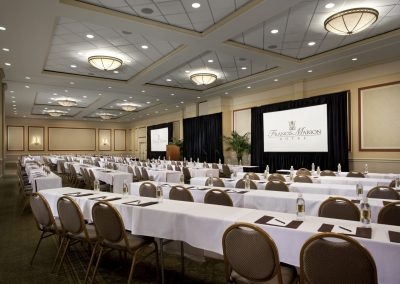 Our Carolina ballrooms has rows of long, rectangular tables et with green and gold chairs face two large projector screens and a stage that has a wooden podium at the front.