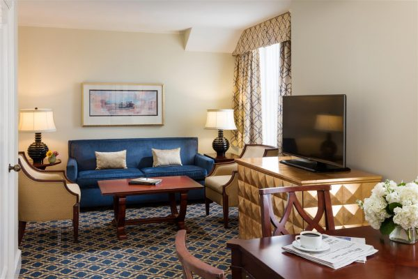 Our Francis Marion Suite features a blue sofa two gold chairs in the living room space. To the right hand side is a small dining table with a few chairs. The space features blue and gold accents throughout.