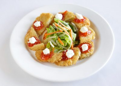 A round white plate with half circle shaped fried green tomatoes with red pepper jelly and a white goat cheese are plated around the edge of the plate. A green salad with shredded carrots and onion sit in a neat pile in the center.