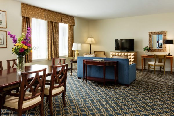 A suite is shown featuring the living and dining room space. Blue and gold accents are throughout the space.