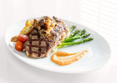 An oval white plate has a large grilled steak on top of roasted potaties and tomatoes. Green asparagus sits under the steak and an orange sauce is neatly smeared in a swoosh to the side.