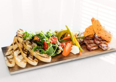 A wooden rectangular board has four slices of grilled bread to the left hand side, a green salad mix with tomatoes and a variety of pickled veggies next to it. Grilled bacon and pimento cheese sit on the end of the board.