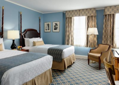 Two double beds are featured with blue and gold accents throughout the room.