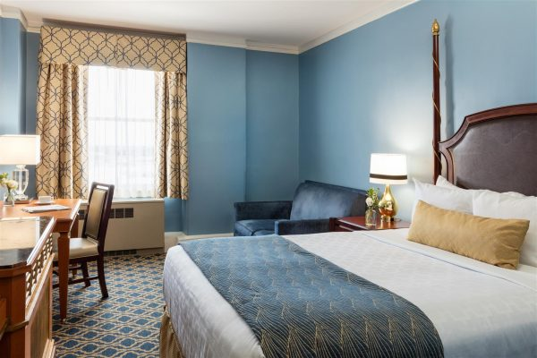 Our traditional room with one queen size bed is featured. Blue and Gold accents are featured throughout. A blue sleeper sofa sits to the right hand side. A small desk is to the left next to a tv console.