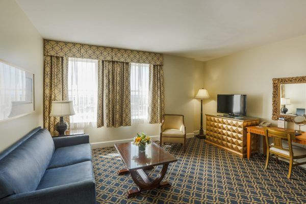 Our downtown view suite shows the living room space that offers a blue sleeper sofa, a wooden coffee table sits in front of it. A desk with a gold chair is to the side with an ornate mirror on the wall.