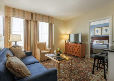 The living room of one of our suites has a blue couch and a yellow chair witha coffee table in the middle. A door leads into the bedroom and shows a neatly made bed.