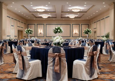 Ballroom of the hotel called the Carolina Ballroom is set with multiple roun tables with blue tablecloths and chairs decorate in blue and mauve ribbons.