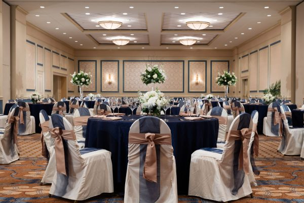 Ballroom of the hotel called the Carolina Ballroom is set with multiple round tables with blue tablecloths and chairs decorate in blue and mauve ribbons.