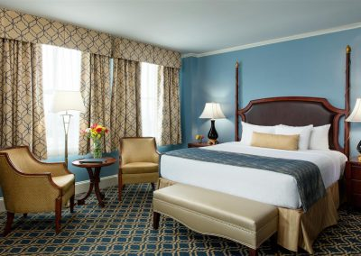 Our deluxe room features bright blue and gold features with a comfortable queen size bed. Two gold chairs are to the side.