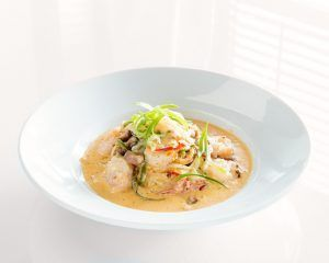 A bowl of shirmp and grits with a creamy orange sauce and green onions sit on top.