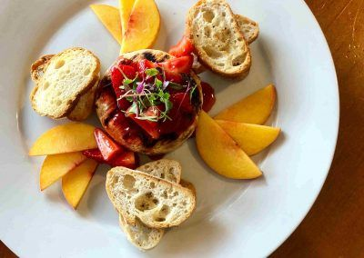 A round white plate sits that has peaches and crostini's around a piece of brie with strawberries on top.