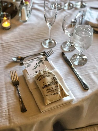 A close up of a place setting includes a personalized bag of grits and a menu.