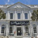 A historic white building with a black banner hangs in the front doors that reads Spoleto Festival USA.