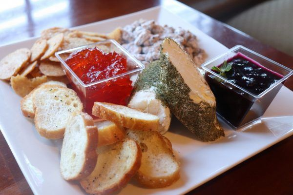 A square plate with crostinis, two different jams and a cheese in the middle.