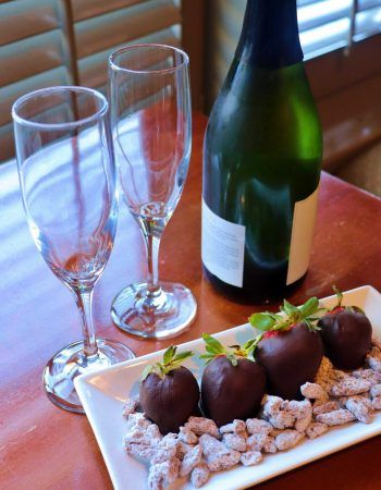 Four chocolate covered strawberries and a bottle of wine and tow glasses.