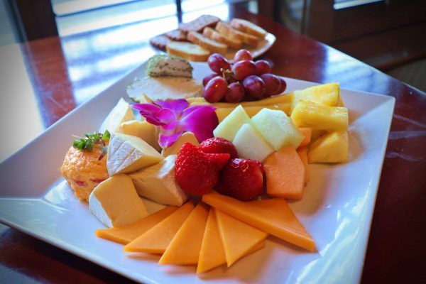 A plate with cheese and fruit.