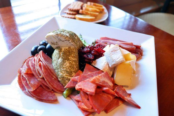 A square plate with a variety of meats and cheeses.