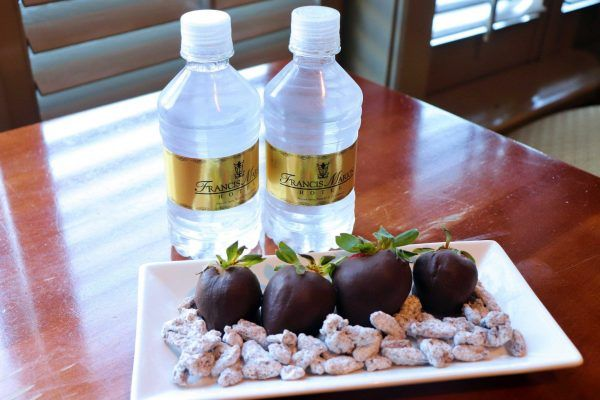 Four chocolate covered strawberries sit on a small rectangular plate. Two small water bottles sit behind the plate.
