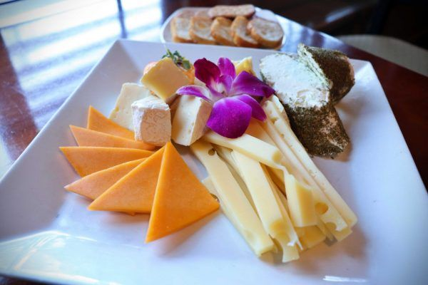 A large plate with a variety of cheeses.