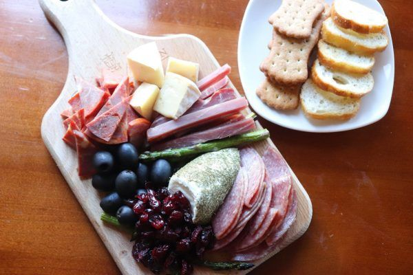 A wooden board with a variety of meats and cheeses.