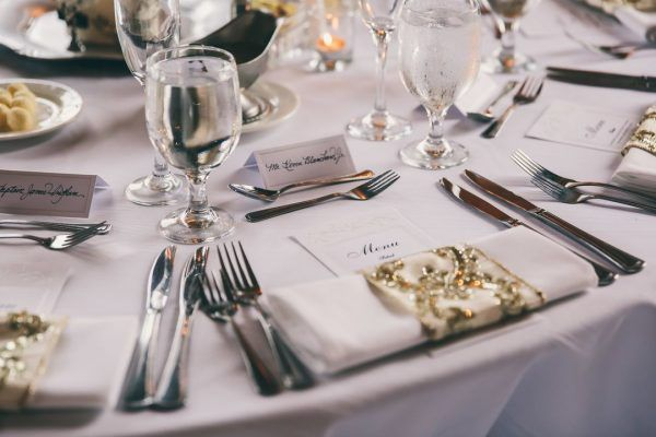 A close up of a table set up for a wedding dinner. A purple tablecloth and matching putpler napling witha gold detail sits on top of their paper menu. Silverware is space around and water glasses sit filled.