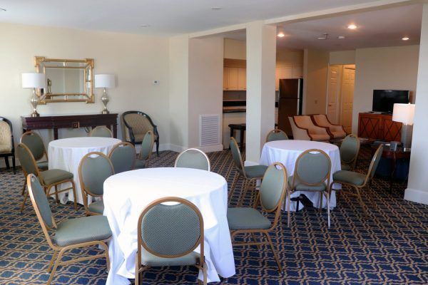 A hotel room suite has three small round tables set with tablecloths and chairs around them. A small kitchen and living room space are to the back side of the space.