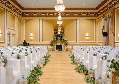Our gold ballroom is set with white chairs with greenery accents in rows for a wedding ceremony. A large ornate mirror is int he center of he room and a piano sits off to the left hand side.