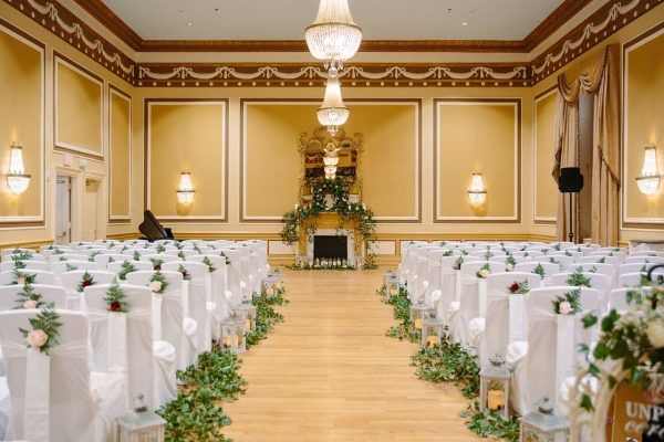 Our gold ballroom is set with white chairs with greenery accents in rows for a wedding ceremony. A large ornate mirror is in the center of he room and a piano sits off to the left hand side.