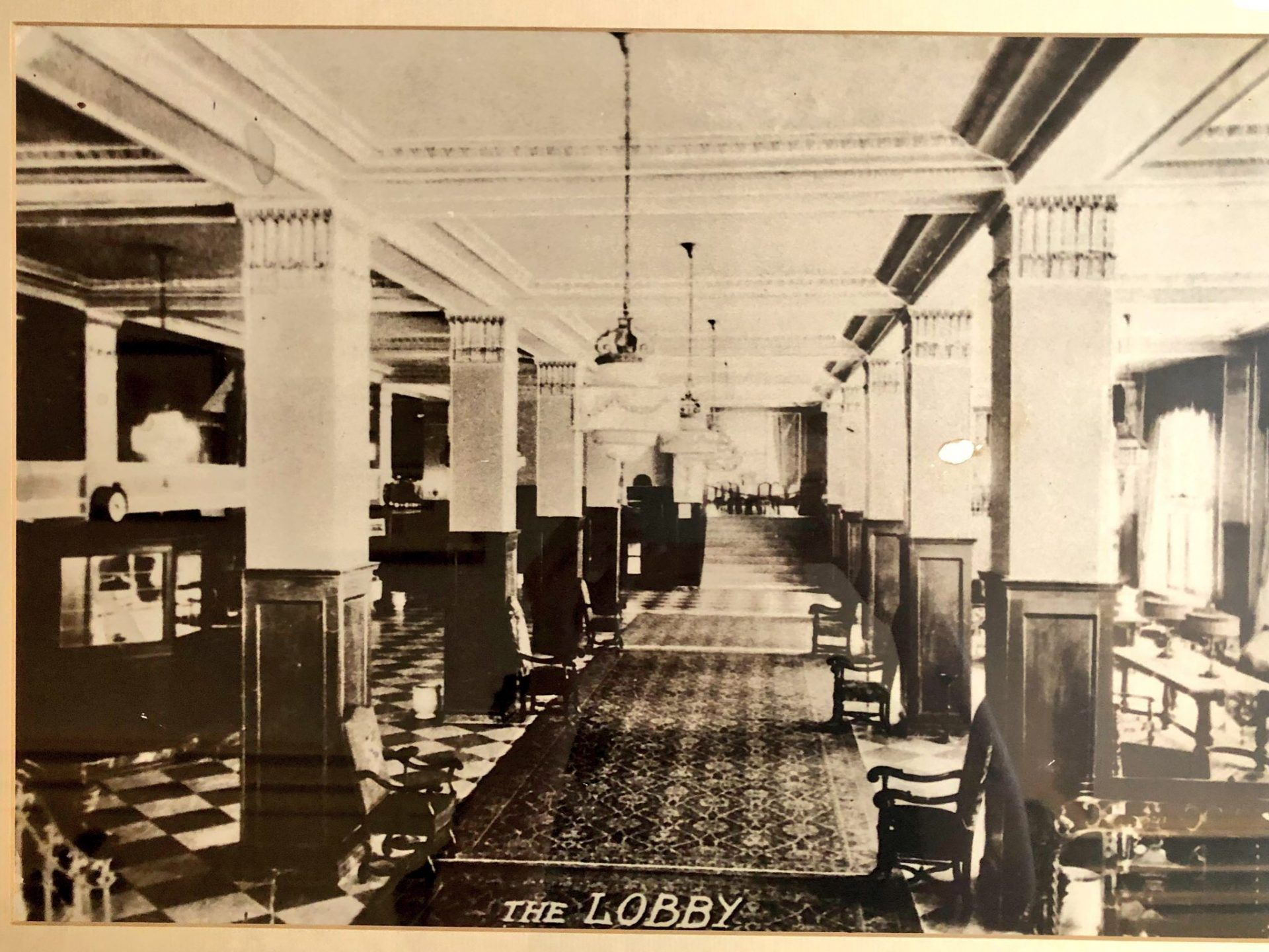 A photo of the original lobby is in sepia and shows square tile flooring and carpeted middle walk ways.