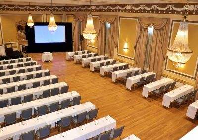 An aerial view of the gold ballroom is set with multiple long rectangle tables with blew chairs. They are facing a large projector screen and a small stage with a podium is to the side.