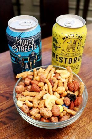 A small bowl of trailmix and two cans of beer sit on a table.