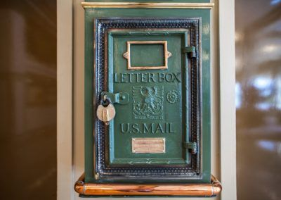 An old green letter box with a golden latch.