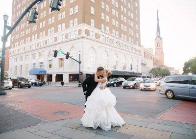 A bride and groom embrace in a kiss on the corner on the street with the hotel in background as traffic goes by