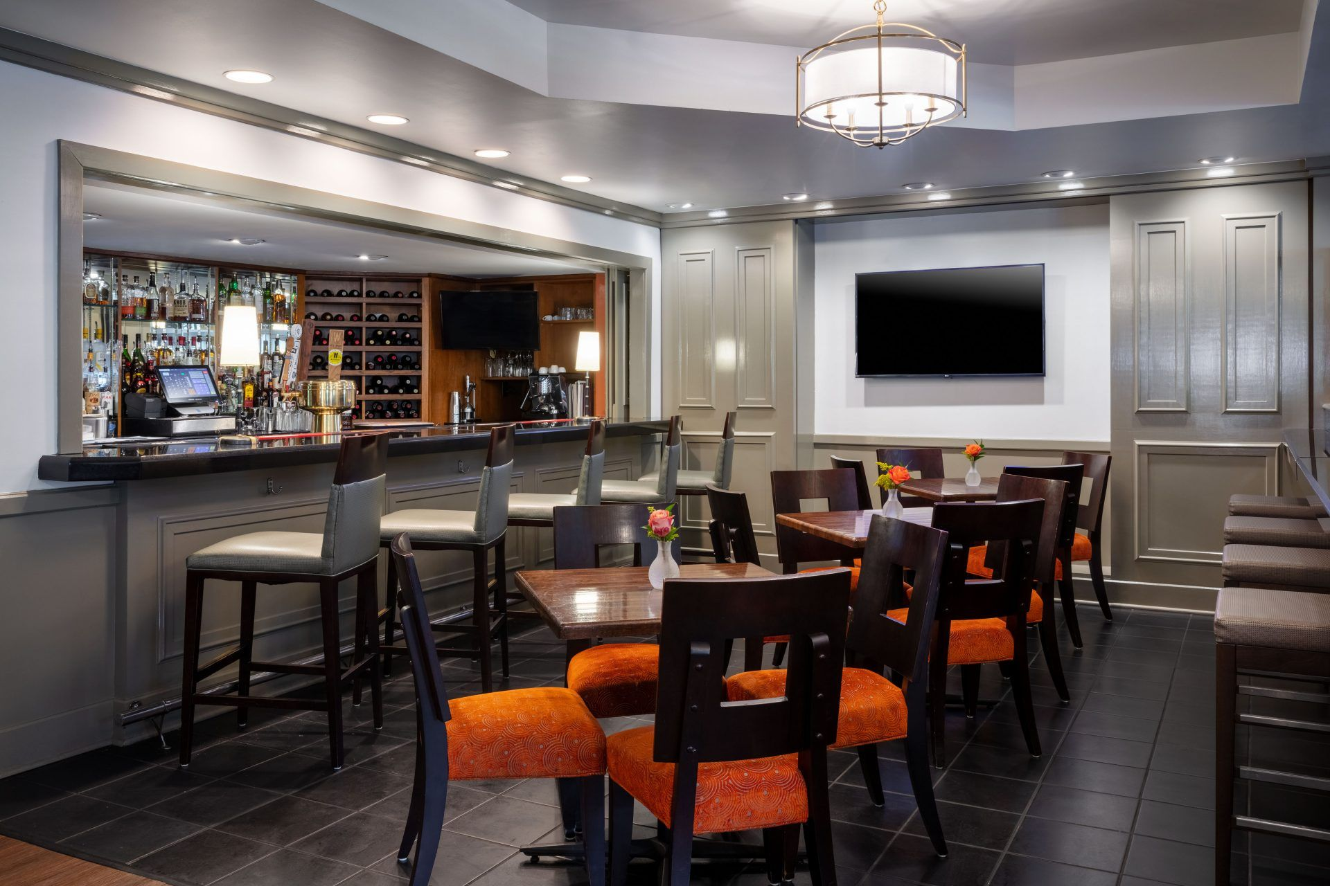 The bar area of the swamp fox restaurant has five bar seats and three tables with four chairs around them. A tv hangs on the wall.