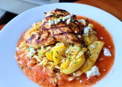 Grilled chicken on a bed of orzo rice with yellow squash and a red sauce in placed on top of a round white plate.