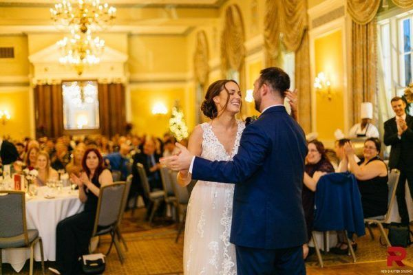 A bride and groom laugh as they dance together as their guests watch and clap.