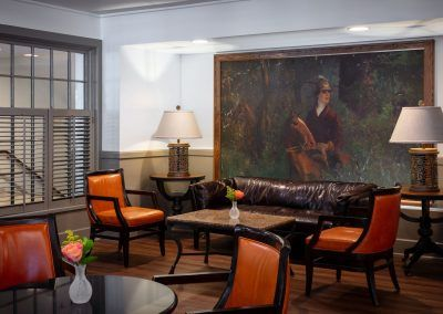 The lounge area of the restaurant shows orange chairs and a brown leather couch up against a wall with a large painting of a man on a horse.