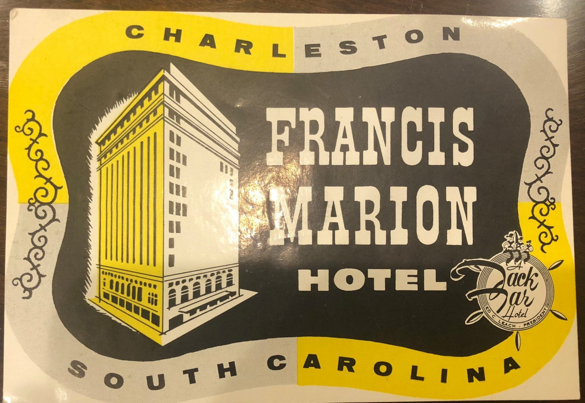 A grey and yellow postcard that reads Charleston, south Carolina. In the middle is a drawing of the exterior of the hotel and says Francis Marion Hotel.