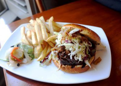 A barbeque sandwich with fries sits on a white plate.