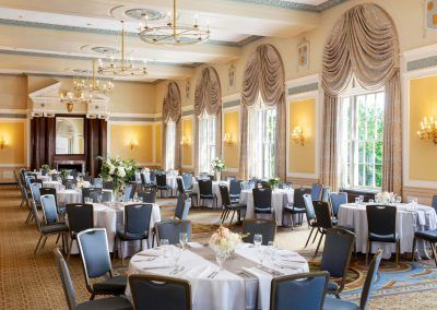 Our colonial ballrooms offers large windows letting in tons of natural light. The rooms is set with multiple large round tables with blue chairs seated around each table. Small floral centerpieces sit in the middle of the tables and an ornate fireplace is in the center of the back wall. Large antique chandeliers hang from the ceiling.