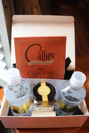 A box is opened and two water bottles with a small jar and a bag that says cheese crisps sits inside.