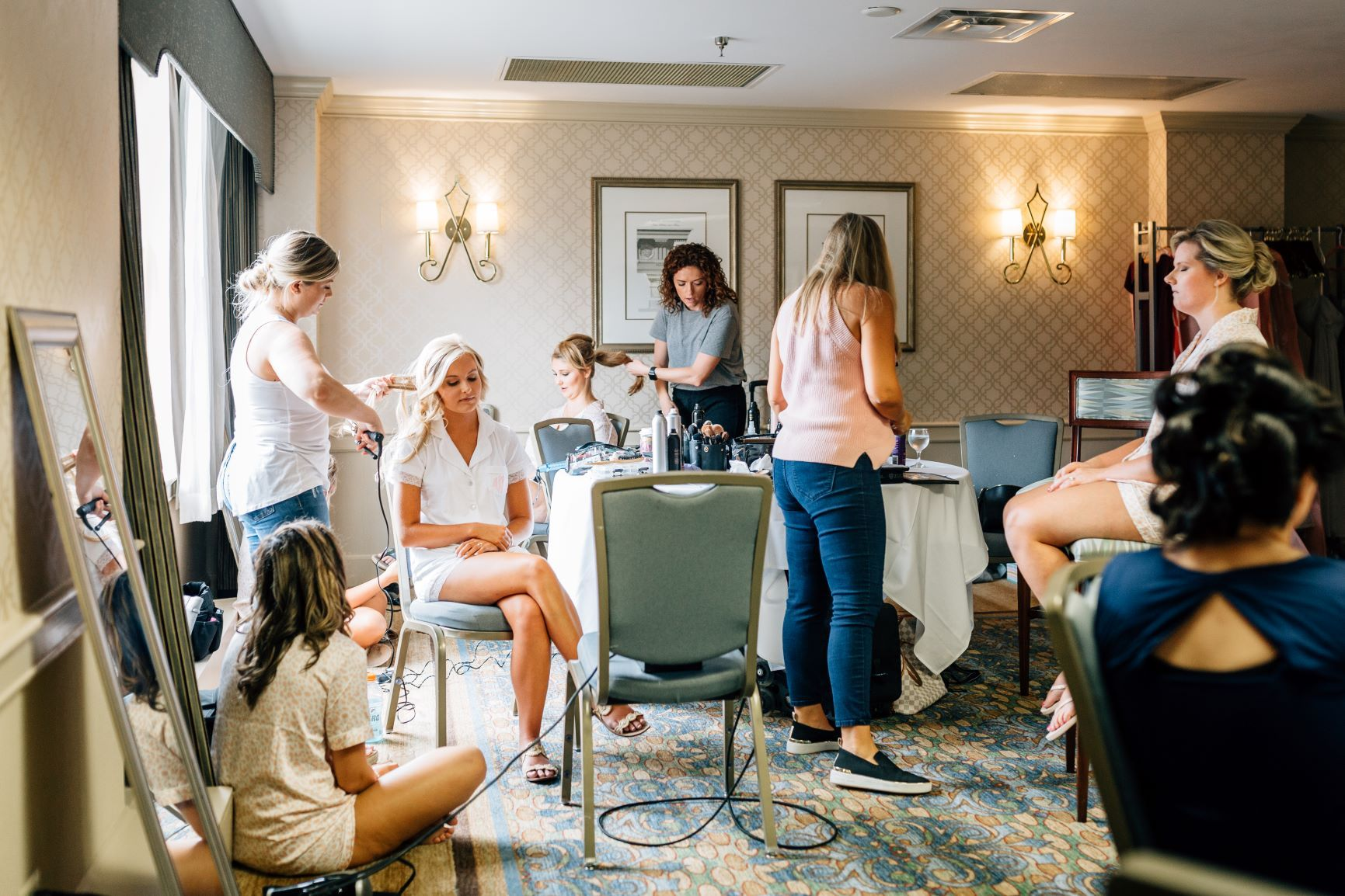 A bridal party gets ready in a room.