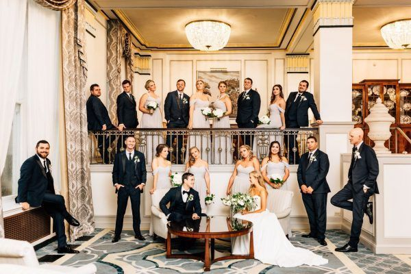 A bridal part is spread-out around the sitting area of the lobby and posing for the camera.
