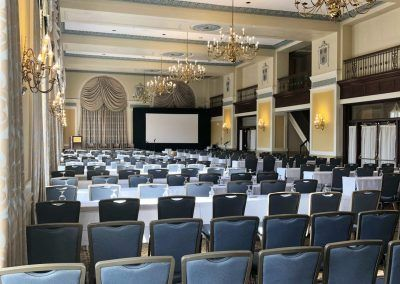A ballroom space with large chandeliers and rows of long tables and chairs.