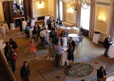 A gathering in a ballroom space. People are mingling and walking around the ballroom that is set with different sized tables.
