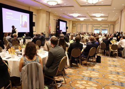 A ballroom in the hotel has a conference taking place and multiple round tables are filled with people listening o a presentation by a man.