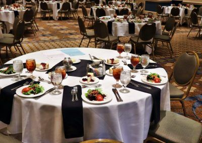 A ballroom with multiple round tables are set with salad, dessert and drinks.