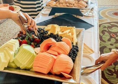 A buffet with a large plate of fruit and two people are using tongs to plate their fruit. A lady behind is grabbing a pastry off another plate and a plate of bagels sits at the end of the table.