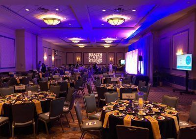 A ballroom space has purple and blue lighting and is set with multiple round tables with salas, dessert and drinks already on the tables. A projector places the words Health Care Heroes on the back wall.