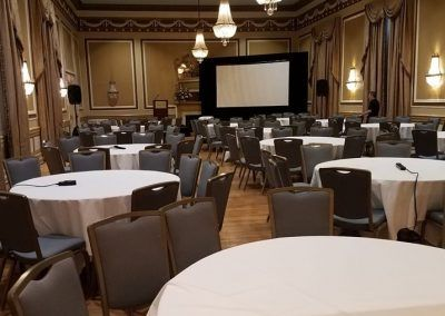 A ballroom space is set with multiple round tables that are bare. A large blank screen is in the back.